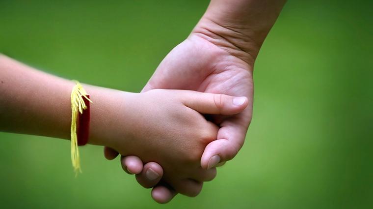 Una nena de la mà de la seva mare